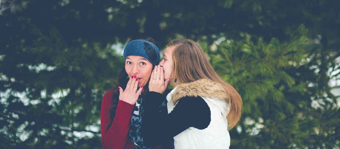 woman whispering on woman's ear while hands on lips