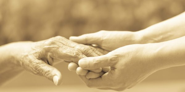 Caregiver, carer hand holding elder hand in hospice care. Philanthropy kindness to disabled old people concept.Happy mother's day.